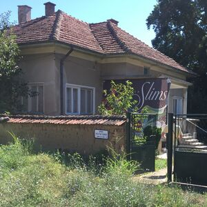 Country house with two garages & land located in big village